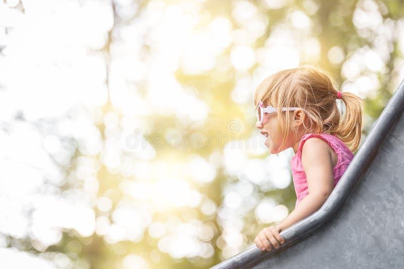 Счастливая белокурая девушка на скольжении стоковое изображение rf