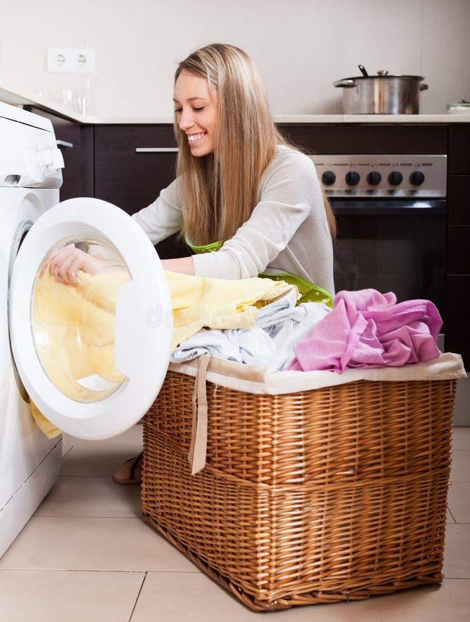 Счастливая белокурая загрузка женщины одевает в стиральную машину стоковые фото