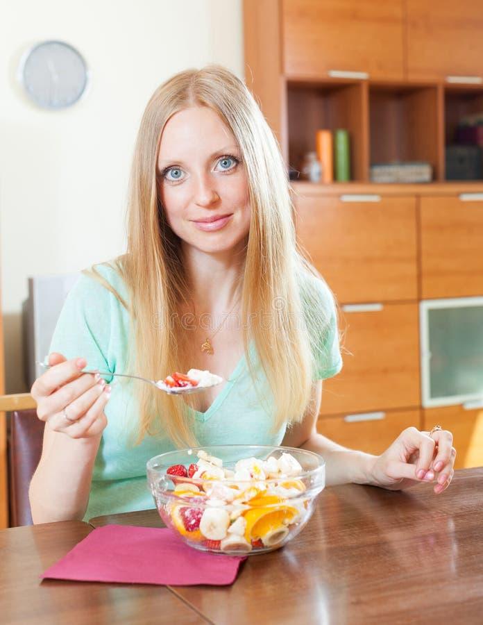 Счастливая белокурая длинн-с волосами женщина есть фруктовый салат с югуртом стоковые изображения rf