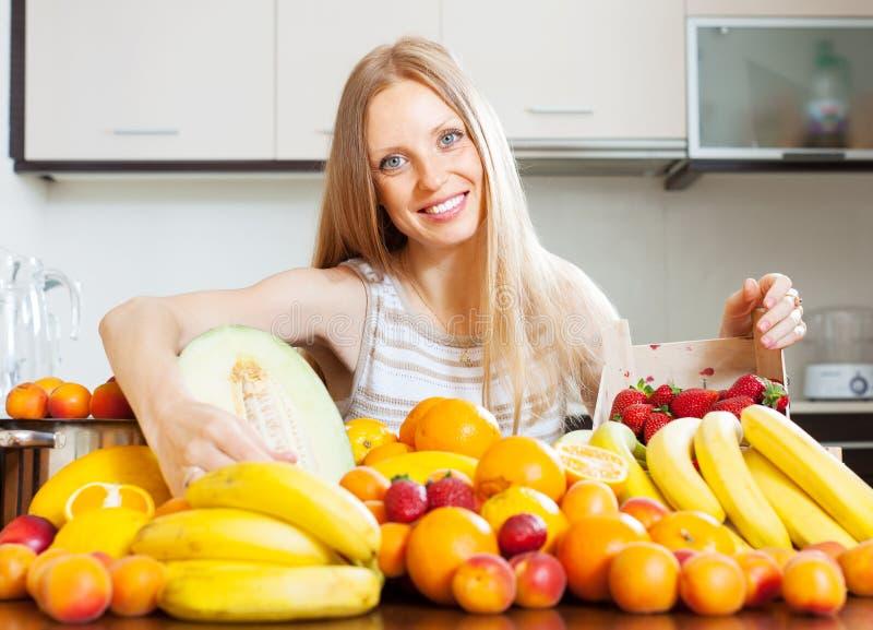 Счастливая белокурая домохозяйка с зрелыми плодоовощами стоковое изображение