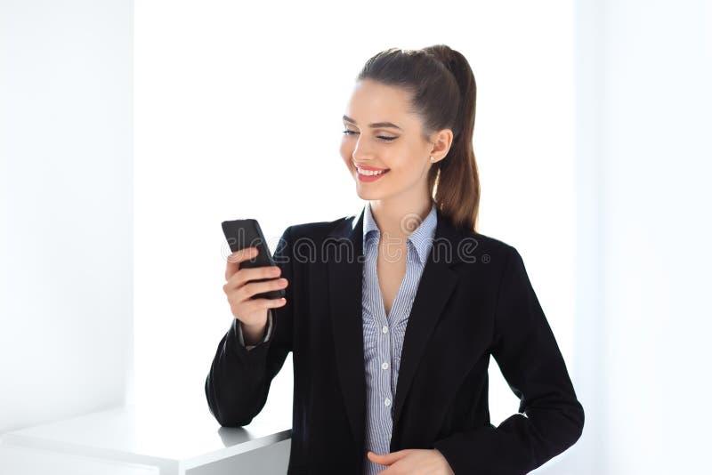 Счастливая бизнес-леди держа мобильный телефон стоковые изображения rf