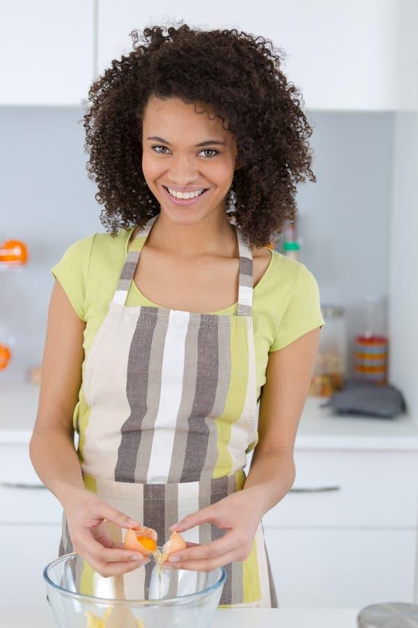 Счастливая выпечка женщины в кухне стоковая фотография