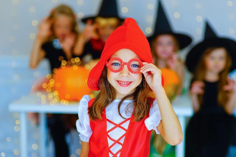Счастливая группа в составе дети в костюмах во время партии хеллоуина стоковое изображение