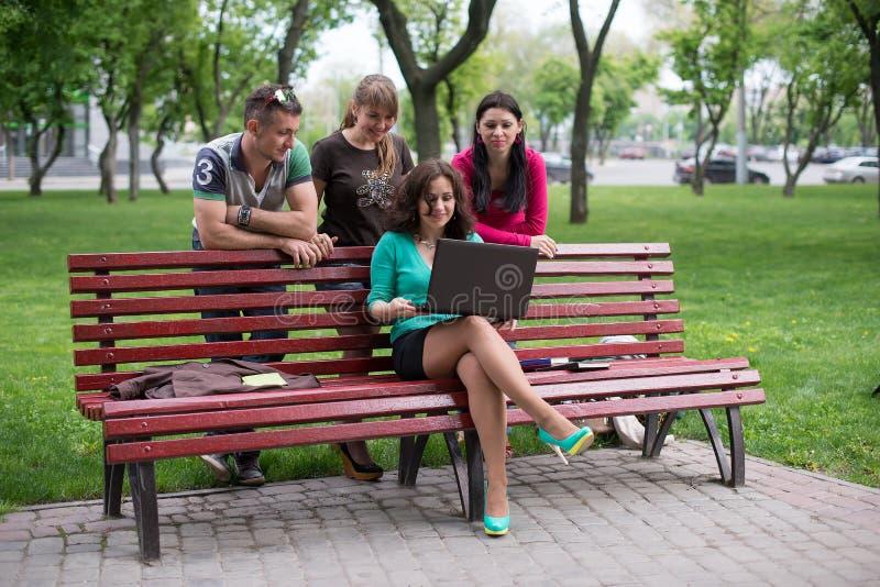 Счастливая группа в составе молодой сидеть студентов стоковое фото