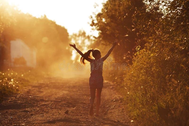 Счастливая девушка бежать на пылевоздушной дороге стоковые фото