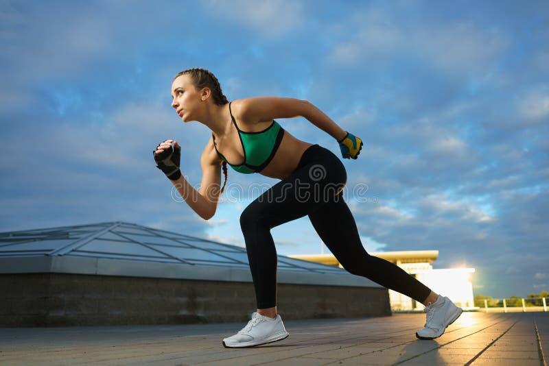 Счастливая девушка бежит внешнее на современной городской местности во время захода солнца стоковые изображения rf