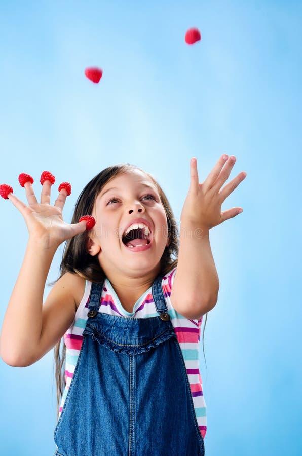 Счастливая девушка играя с ее плодоовощ стоковая фотография rf