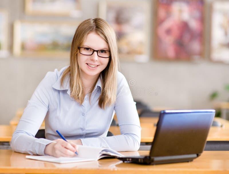 Счастливая девушка используя компьютер в библиотеке. стоковое изображение rf