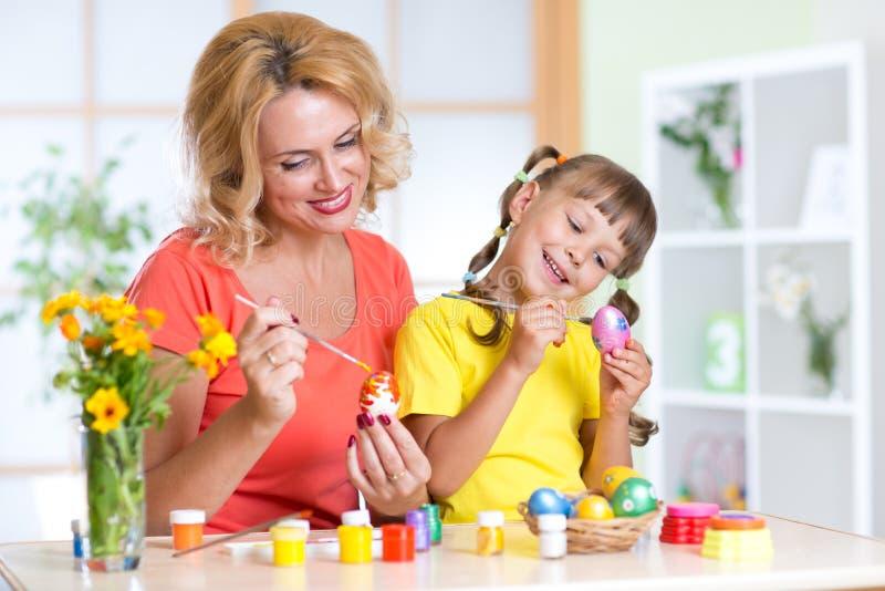 Счастливая девушка матери и ребенка подготавливая к празднику пасхи и с яичками расцветки щетки стоковая фотография