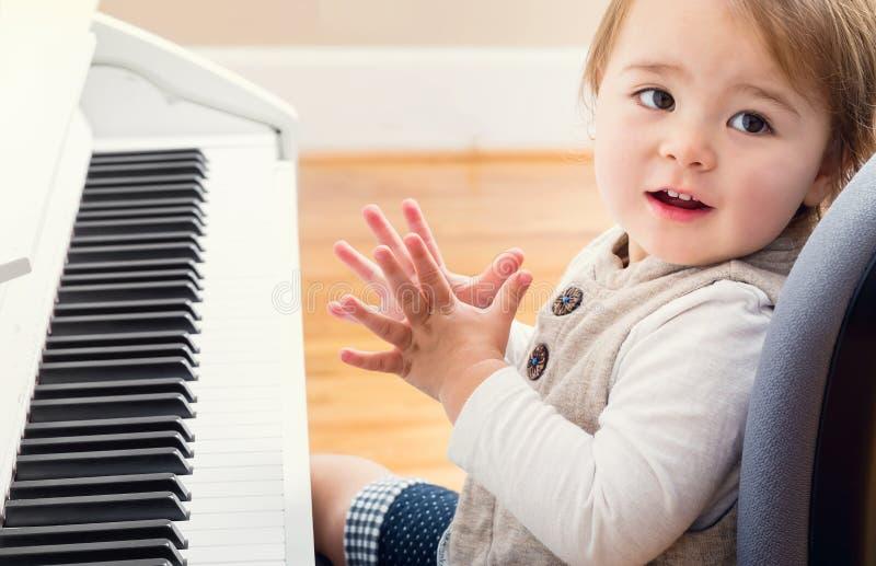 Счастливая девушка малыша играя рояль стоковые фото