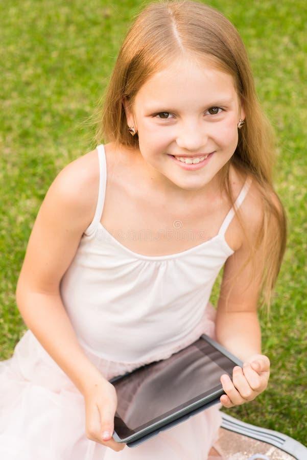 Счастливая девушка на траве при планшет смотря камеру стоковое фото rf