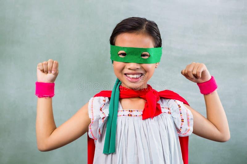 Счастливая девушка одетая как супергерой в классе стоковое фото