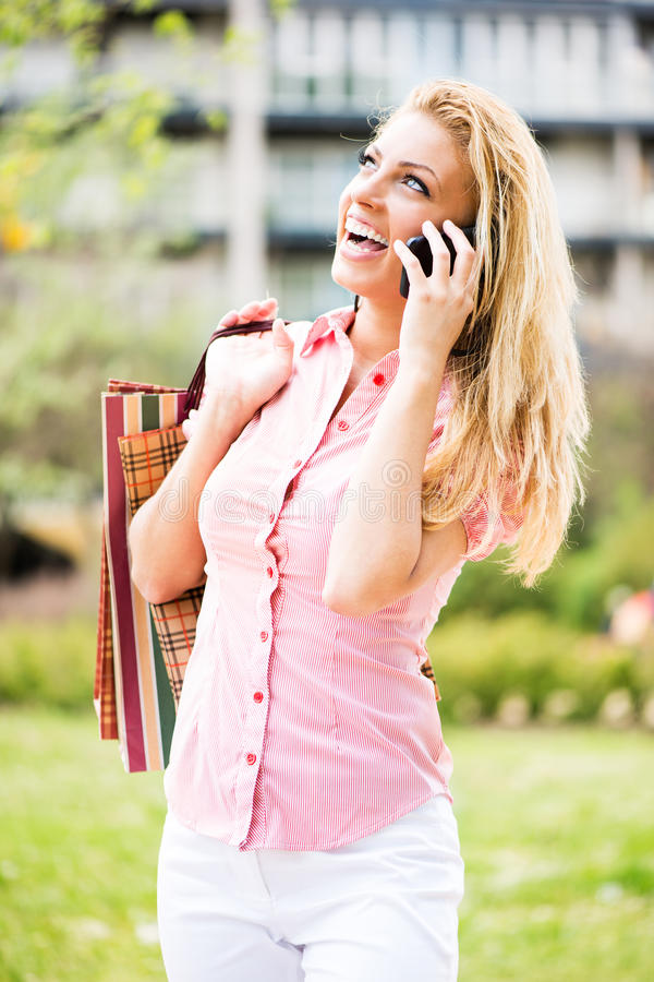 Счастливая девушка при хозяйственные сумки имея телефонный звонок стоковые изображения