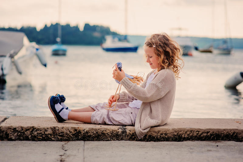Счастливая девушка ребенка играя с птицей игрушки на береге моря лета стоковое изображение rf