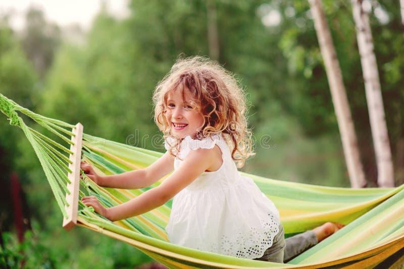 Счастливая девушка ребенка имея потеху и ослабляя в гамаке в лете стоковая фотография rf