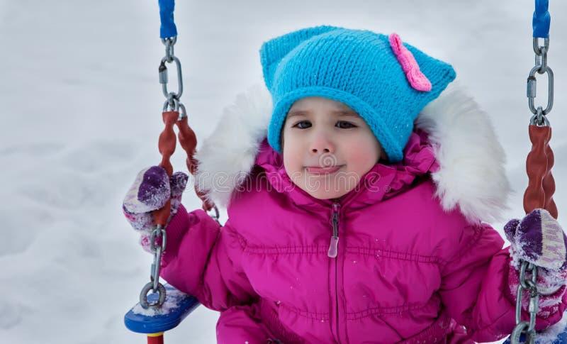 Счастливая девушка ребенка на качании в зиме захода солнца Маленький ребенок играя на прогулке зимы в природе стоковое изображение