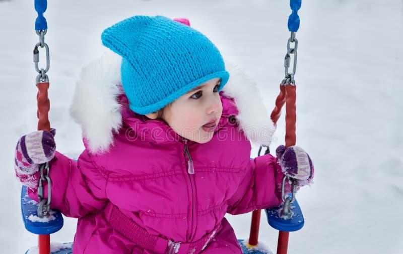 Счастливая девушка ребенка на качании в зиме захода солнца Маленький ребенок играя на прогулке зимы в природе стоковая фотография rf