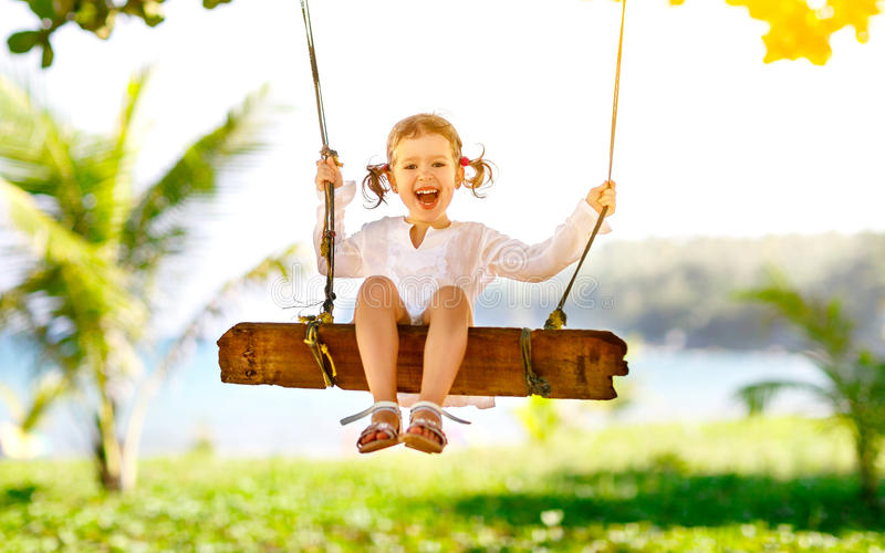 Счастливая девушка ребенка отбрасывая на качании на пляже в лете стоковая фотография rf