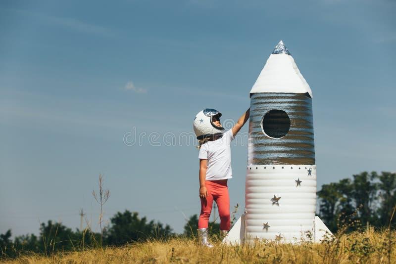 Счастливая девушка ребенка одела в костюме астронавта играя с ручной работы ракетой Лето напольное стоковое изображение