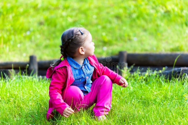 Счастливая девушка ребенка сидя на зеленой траве стоковое фото rf