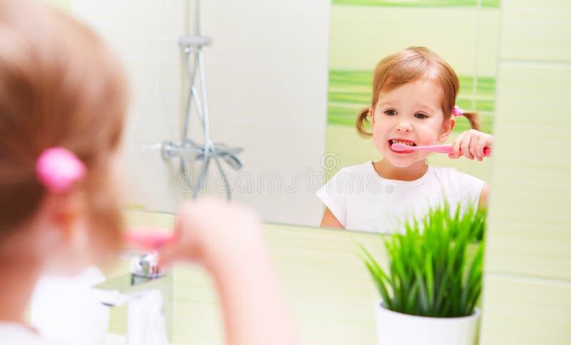 Счастливая девушка ребенка чистя ее зубные щетки щеткой зубов в ванной комнате стоковая фотография