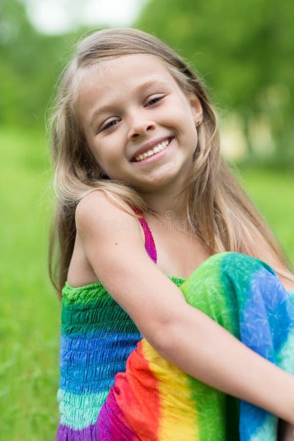 Счастливая девушка сидя на траве стоковая фотография rf