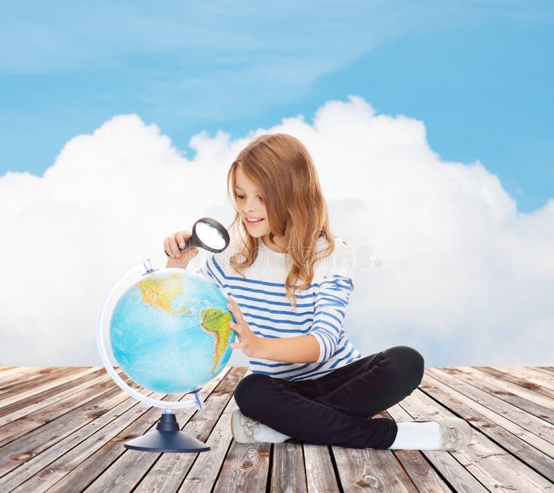 Счастливая девушка смотря глобус с увеличителем стоковая фотография