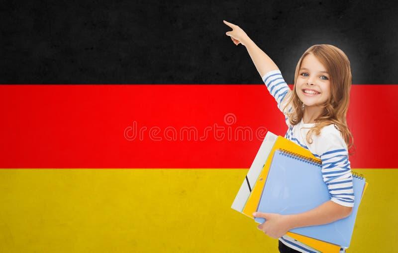 Счастливая девушка студента с папками указывая палец стоковая фотография rf
