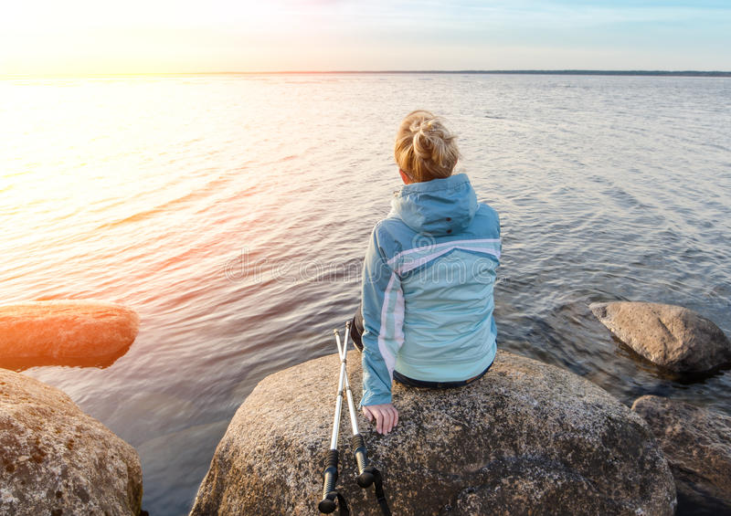 Счастливая девушка с пешими ручками на озере на утесах эстония стоковые изображения