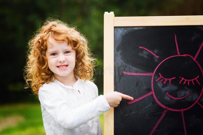 Счастливая девушка указывает палец на изображение с счастливым солнцем, pai стоковое фото