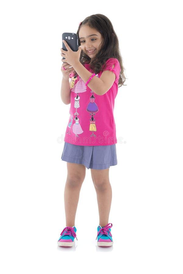 Счастливая девушка фотографируя с камерой телефона стоковое изображение
