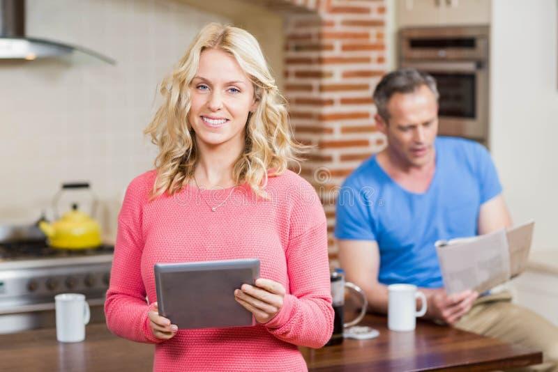 Счастливая жена используя таблетку пока газета чтения супруга стоковое изображение rf