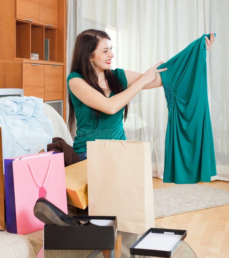 Счастливая женщина брюнет смотря новое зеленое платье стоковые фото