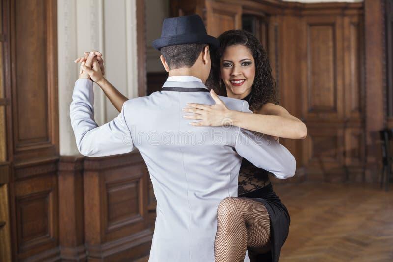 Счастливая женщина выполняя с мужским танцором танго стоковое изображение rf