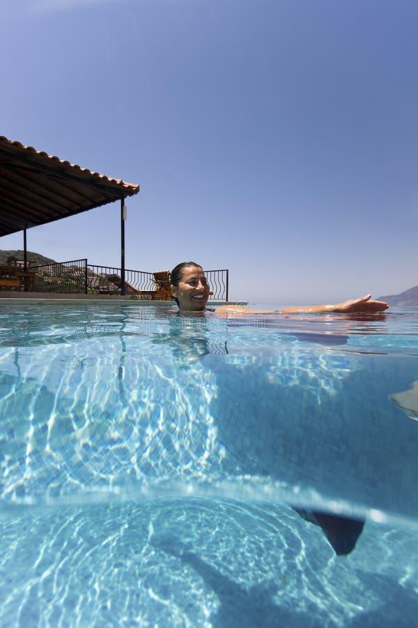 Счастливая женщина в бассейне стоковая фотография