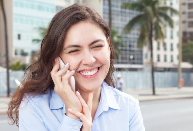 Счастливая женщина в голубой блузке на телефоне в городе стоковое изображение