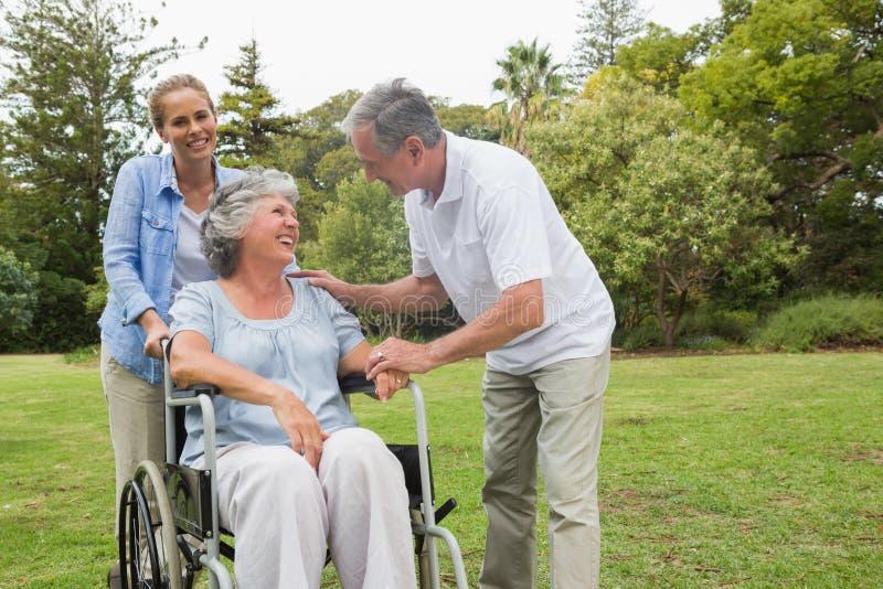 Счастливая женщина в кресло-коляске с супругом и дочерью стоковая фотография