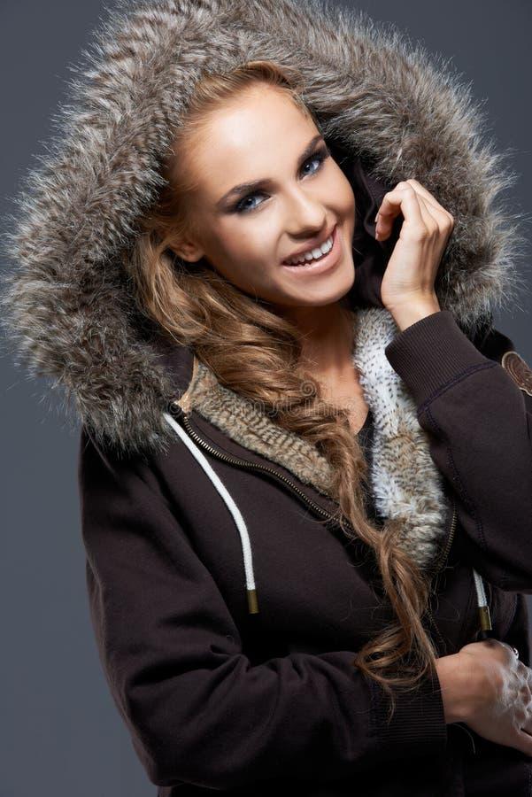 Счастливая женщина в куртке с меховым клобуком стоковое изображение rf
