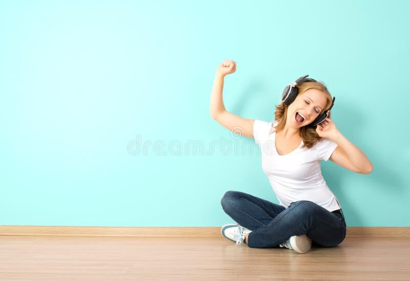 Счастливая женщина в наушниках слушая к музыке в комнате с b стоковые изображения