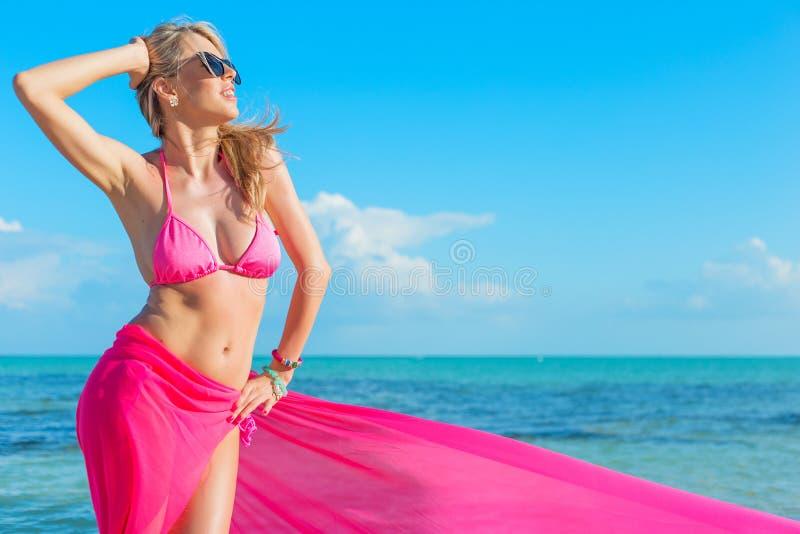 Счастливая женщина в розовом бикини предусматриванном с частью ткани стоковая фотография rf