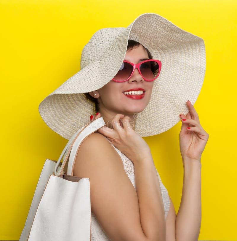 Счастливая женщина в стеклах шляпы и солнца стоковые изображения