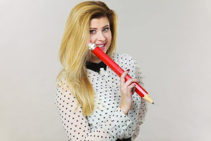 Счастливая женщина держа большой слишком большой карандаш стоковое фото