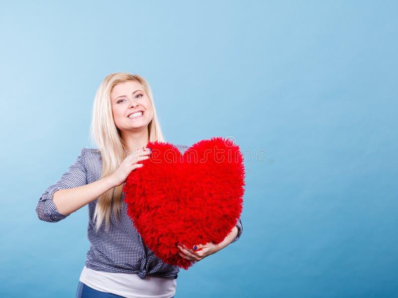 Счастливая женщина держа красную подушку в форме сердца стоковая фотография