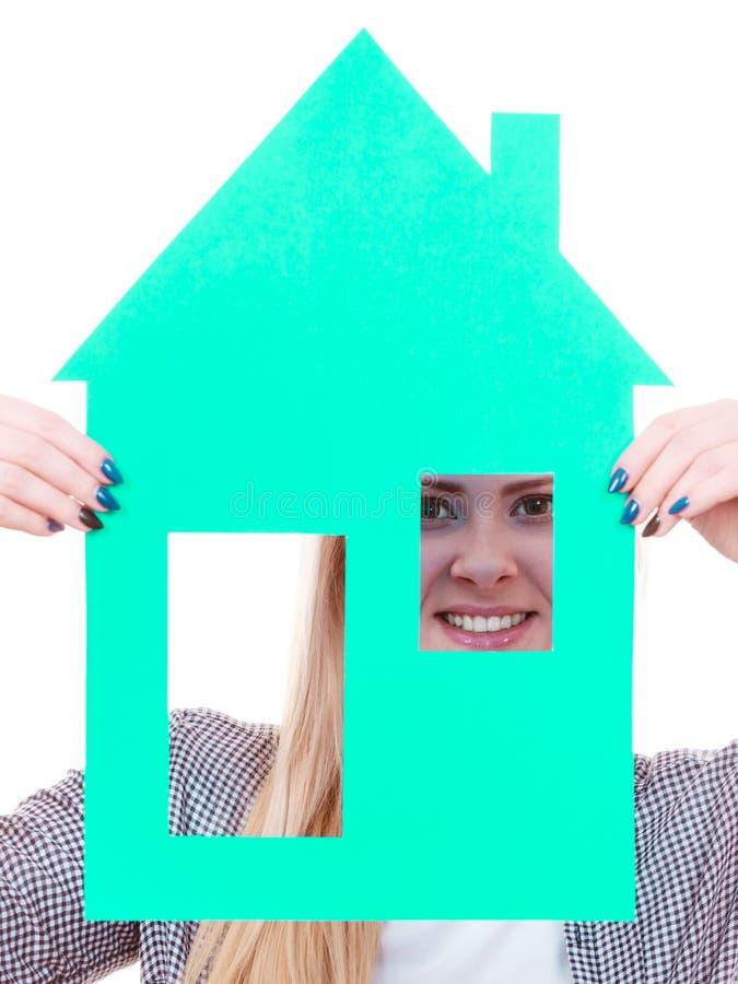 Счастливая женщина держа дом голубой бумаги стоковая фотография rf