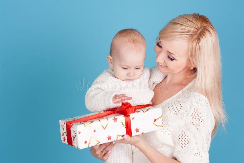 Счастливая женщина держа ребёнок с подарком на рождество стоковое изображение rf