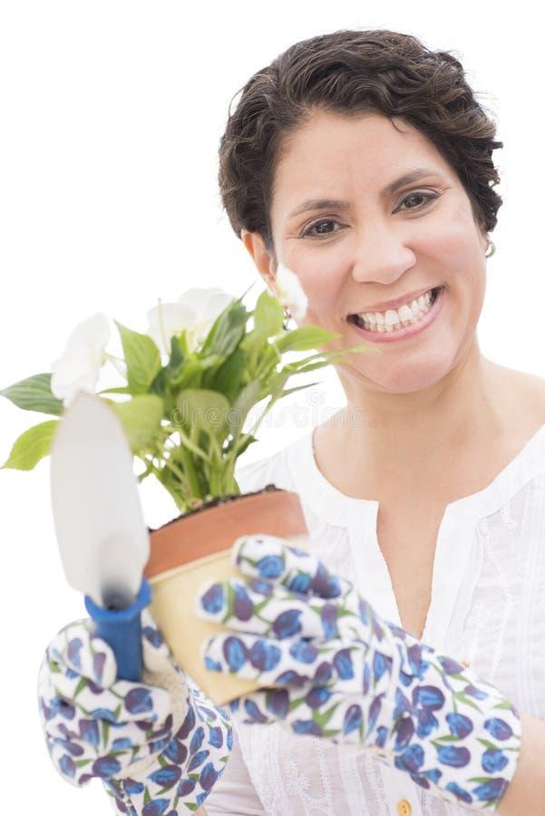 Счастливая женщина держа цветочный горшок и лопаткоулавливатель стоковые фото