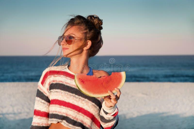 Счастливая женщина есть арбуз на пляже стоковое фото