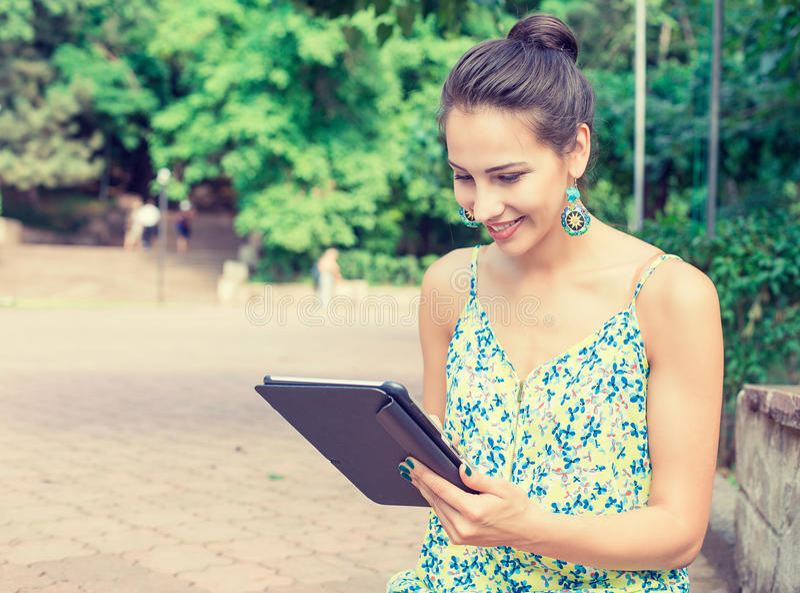 Счастливая женщина используя планшет внешний в парке лета, усмехаясь стоковое изображение rf