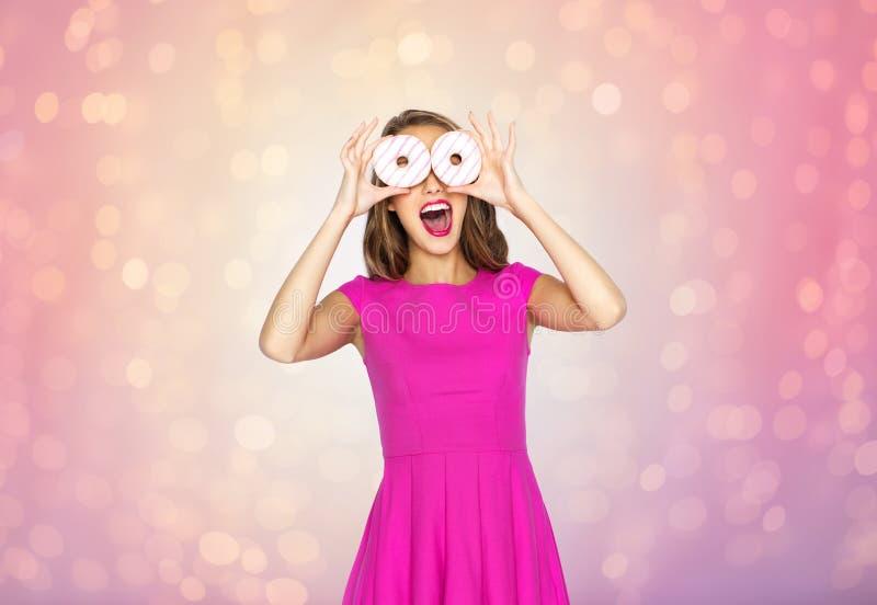 Счастливая женщина или предназначенная для подростков девушка имея потеху с donuts стоковое изображение