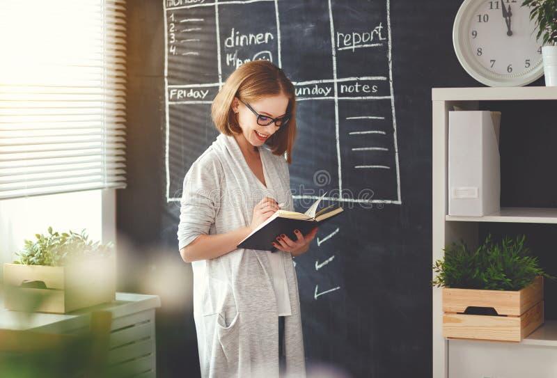 Счастливая женщина коммерсантки на школьном правлении с планированием план-графика стоковая фотография
